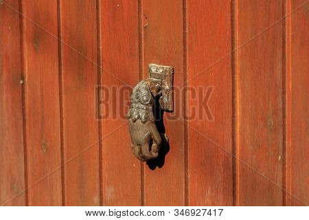 Hand Shaped Door Knocker On Wooden Door