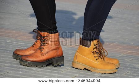 Girls In Shoes, Half-boots Are Standing On The Sidewalk Tiles, In A Sunny Evening. A Quarrel Between