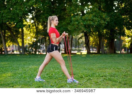 Young Woman Is Training With Rubber Bands Outdoors. Healthy Active Lifestyle Concept. Girl Doing Fit