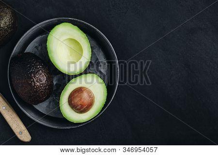 Raw Avocado On Dark Stone Background. Fresh Green Ripe Avocado For Guacamole.