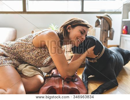 Woman Caressing Her Dog At Home.