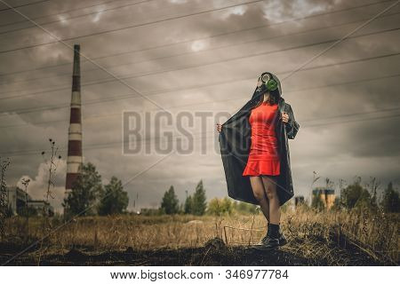 Woman In Gas Mask Red Dress And Raincoat Among Burnt Field Over Factory Chimney Background.