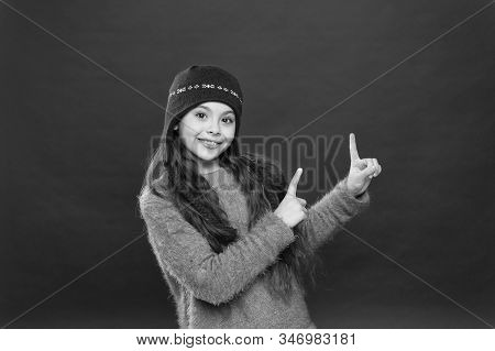 Winter Sale. Happy Girl In Warm Hat Pointing Index Fingers At Something. Small Child Smiling And Poi