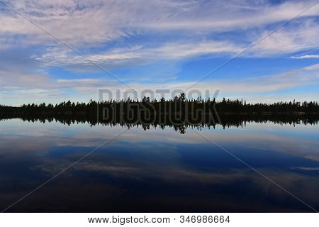 Dramatic Mirrored Silhouette Of A Boreal Forest Tree Line And A Cloudy Blue Sky In Cirrus Lake, Quet