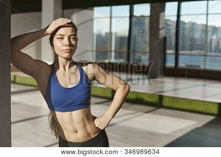 Athletic And Strong Good-looking Young Fitness Instructor, Sportswomen In Sportsbra, Showing Six-pac