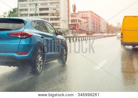 Cars Moving Fast By Wet Highway After Heavy Rain With Warm Sunset Evening Sun On Background. Vehicle