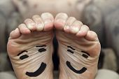 Funny image of a pair of bare male feet with happy smiley face drawn on bottom poster