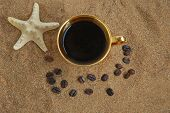 Gold cup with coffee beans and starfish on a sea beach poster