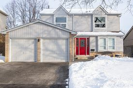 Typical Suburban Detached House With Grey Siding And Red Door After Snow
