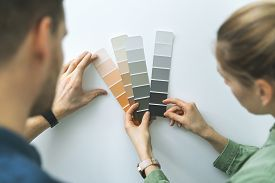 Young Couple Choosing Paint Color From Samples For New Home Interior Design