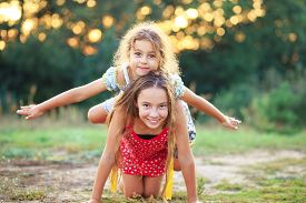 Two Cute Little Girls Playing And Laughing At The Countryside. Happy Kids Outdoors Concept
