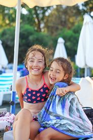 Two Cute Little Girls Hugging And Smiling At The Seaside At Sunset.  Summer Sunny Day, Ocean Coast,