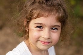 Portrait Of Smiling Beautiful Little Girl At Green Of Summer Park.cute Child Looking At The Camera