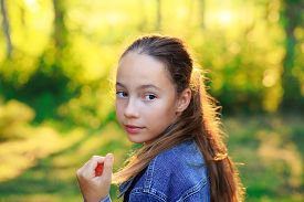 Beautiful Teen Girl Is Looking At The Camera And Smiling At The Park In Summer Sunset