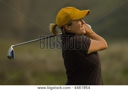 Female Collegiate Golfer Swinging A Golf Club
