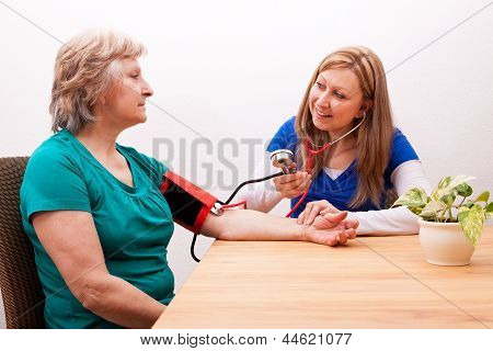 Nurse Measures Senior The Blood Pressure