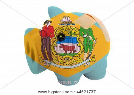Closed Piggy Rich Bank With Bandage In Colors Flag Of American State Of Delaware