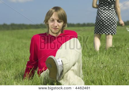 The Young Couple Relaxing On A Meadow