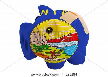 Closed Piggy Rich Bank With Bandage In Colors Flag Of American State Of Montana