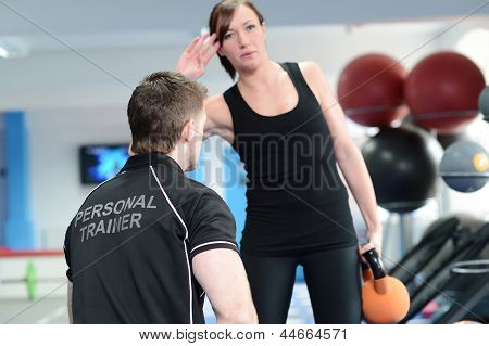 Young Woman Exercising With Fitness Instructor