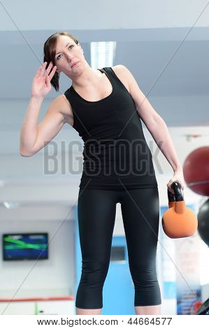 Young Woman Stretching With Kettle Bell Weight