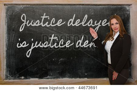 Successful beautiful and confident woman showing Justice delayed is justice denied on blackboard poster