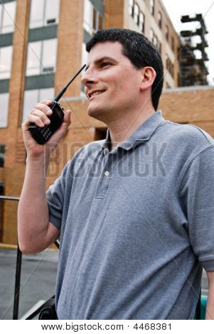 This is a male FCC licensed emergency communications operator with dark hair and dressed casually in a gray shirt who was participating in a federal homeland security drill. The operator is responsible for the communication with military secured lines and poster