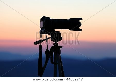 Silhouette of a camera on tripod