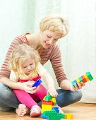 Mother with a little daughter playing with blocks poster