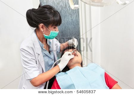 Young female dentist doing examination on her patient teeth