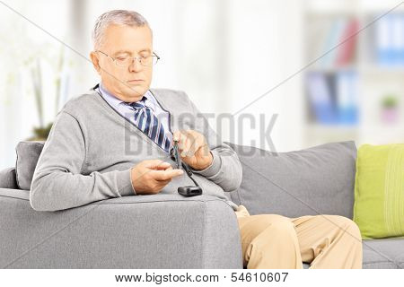 Mature diabetic patient seated on a sofa measuring sugar level in blood using glucometer at home