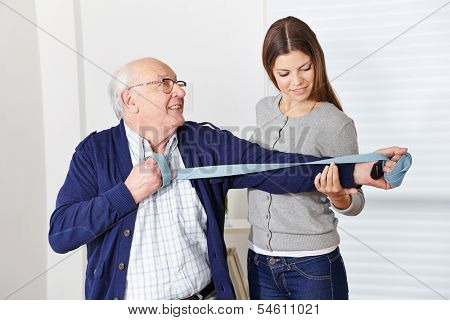 Old senior man exercising at rehabilitation in physiotherapy