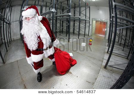 The last,tired Santa Claus loosing gifts from red sack leaving empty storehouse