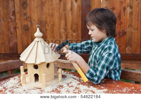 Boy building a bird house - mounting the last roof piece with a nail and hammer