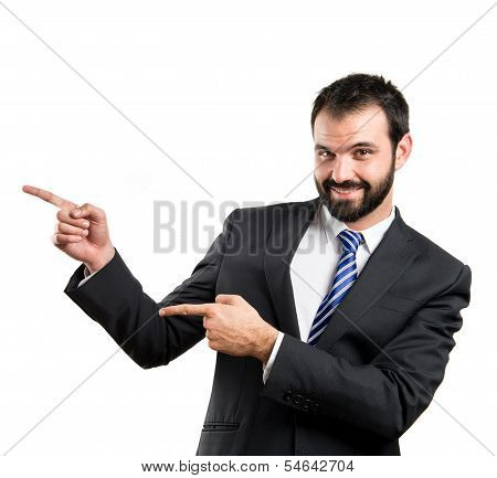 Businessman Pointing To The Side Over White Background