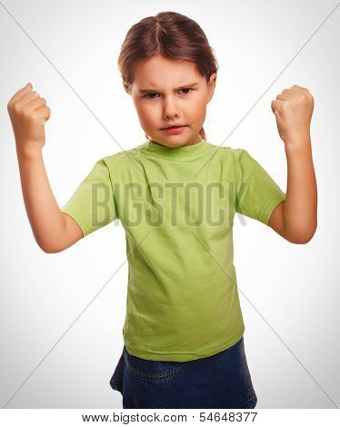 Angry child evil girl shows fists experiencing anger emociones