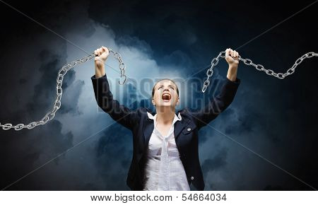 Image of businesswoman in anger breaking metal chain