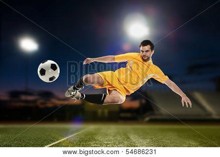 Soccer Player kicking the ball ina football stadium at night