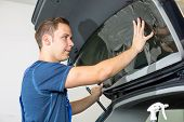 Car wrappers tinting a vehicle window with a tinted foil or film using heat gun and squeegee poster