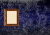 Empty baroque picture frame with copyspace on a dark blue grunge stucco wall poster
