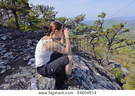 Woman With Binoculars On A Mountain