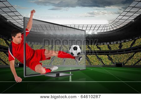 Composite image of fit football player kicking ball through tv against large football stadium with fans in yellow