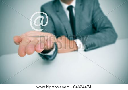 a businessman sitting in a desk with an at sign in his hand, depicting the concept of e-mail service