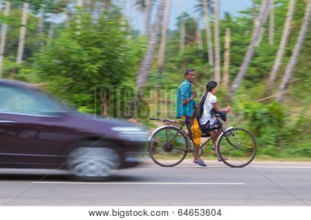 WELIGAMA, SRI LANKA - MARCH 7, 2014: Couple riding a bicycle on local road. Tourism and fishing are two main business in this town.