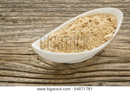 maca root powder in a small ceramic bowl against grained wood