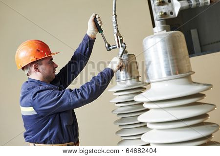 Electrician lineman repairman worker at huge power industrial transformer installation work