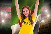 Pretty football fan in brasil t-shirt holding algeria flag against vast football stadium with fans in yellow and red poster
