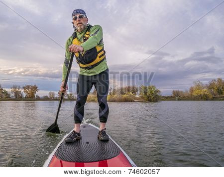 senior paddler in life jacket enjoying stand up paddling on lake, fall scenery in Fort Collins, Colorado