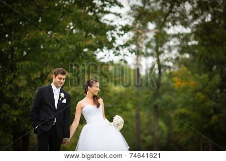Just married, young wedding couple in a park, walking, savoring the moment on her big day (shallow DOF)
