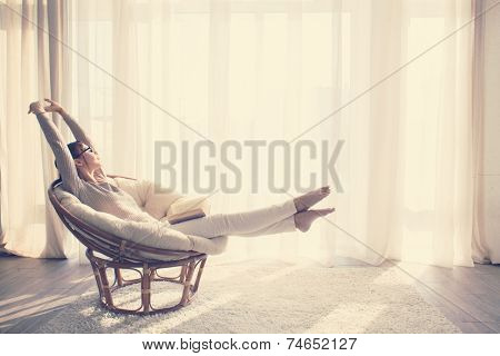 Young woman at home sitting on modern chair in front of window relaxing in her living room reading book